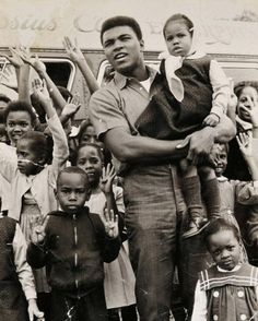 Muhammad Ali holding Malcolm X's daughter Qubilah, surrounded by young fans at his training camp in Miami, January 1964. The kids are holding up 8 fingers because Muhammad predicated he'd win the...
