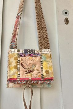 Mixed media unique crossbody bag with an artsy earthy nature vibe Handmade using recycled textiles including wool snippets, vintage needle point, cotton, painted canvas, leather and lace. Handstitched edges Features an interior denim pocket and back leather pocket (for ease in finding
