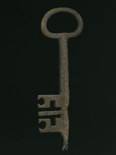 Key Iron key: solid hexagonal shank, narrows at bit with broken pin; ovate bow; bit has symmetrical clefts including circular clefts, one thin ward down center.   Production Date: Late Medieval; 15th century