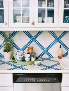 modern hand-painted moroccan tiles Laying the same tiles on counter and backsplash creates a seamless field (and we love the surprise of exotic, hand-painted Moroccan tiles in an all-white country kitchen).