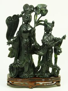 CHINESE CARVED JADE DOUBLE QUAN YIN GROUP  Old Chinese fully relief carved group figure depicting Guan Yin holding leaf fan and leaf pads with young girl holding incense burner. Deep spinach jade color. Includes fitted wooden base. 19th/20th century.