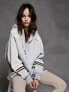 Varsity Embellished Pullover   Super comfy and cozy pullover hoodie with floral embroidery and bead and sequin embellishment on the shoulders. Pieced with contrast thermal on the sleeves and athletic-inspired striped trim on the cuffs. V-neckline and front kangaroo pocket with raw trim throughout.