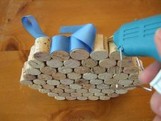 How to make a wine cork trivet    Supplies    31 wine corks (all the same height)  1-1/2 yards of 7/8-inch-wide ribbon    Tools    hot glue gun & glue  scissors  fine sand paper  sharp serrated kitchen knife  cutting board      1. Cut each wine cork in half with the kitchen knife. Try to cut as close to the middle as possible, so each will be the same height.    2. Sand