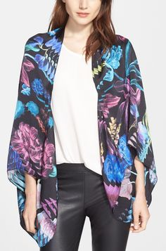 Adding some flair to the fall wardrobe with this dramatic floral silk cape that also doubles as a stylish scarf.