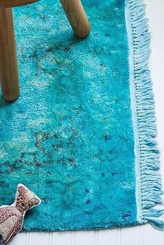 Dye a thrift-store rug using a spray bottle and a plastic tarp.
