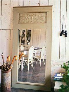 The bottom panel was removed from this heavy vintage door, and replaced with a large mirror. It leans against the wall in this mudroom and reflects light into the kitchen.