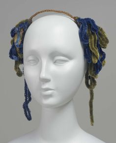 Hair ornament; brown chenille-covered wire to pass over top of head with, at each end, pendent loops of blue and olive green heavy chenille.