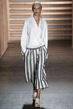Tibi Spring 2015: An oversized wrap button down shirt with blue and white striped culottes worn with white peep-toe flatform shoes.
