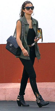 Selena Gomez in olive vest with black shirt and black jeans with Chanel bag and Jeffery Campbell boots.