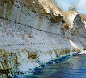 """Flintminedrift – et risikabelt erhverv. Produktionen af de store, slebne flintøkser krævede flint af den bedste kvalitet. For at dække behovet for flint rakte fritliggende blokke af stenarten slet ikke. Derfor benyttede man sig, hvor de geologiske forhold var til det, af regulær minedrift – """"flintminedrift"""". Sådanne miner er eksempelvis lokaliseret ved Hov i Nordjylland. Her har man ved arkæologiske udgravninger fundet snesevis af nedgravede skakter. Stenaldermenneskene har gravet…"""