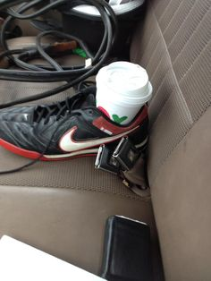 Create a cup holder out of a running show. DIY Car Hacks done right. Avoid using an old shoe though!