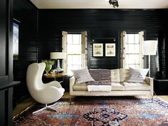 Rustic and urbane, under-the-radar and outright seductive—these glossy black wood-paneled walls fit right in to our recent sexy cabin obsession. Pairing them with midcentury furnishings in luxe neutrals and an ornate carpet softens the whole look.