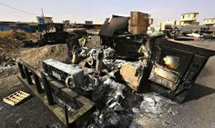 Burnt vehicles belonging to Iraqi security forces at a checkpoint in east Mosul, after insurgents seized control of the city. Photograph: Re...