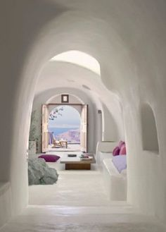 Greek Isles cave house: I would SOO love a house with arcitecture like this! And the purple in all of it is stunning. Look at that balcony and the doors leading to it! Breathtaking!