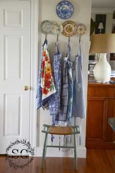 Love the vintage aprons hanging in the kitchen...and that plate hook is too pretty!!!   2013 Summer House Tour stonegableblog.com 21