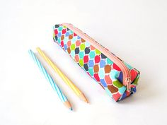 A small pencil case made out of cotton fabrics. Fits about 20 standard pencils, with some extra room for your eraser or sharpener. It can also be used to store make-up brushes or knitting/crochet needles or other thin, long items. The outer fabric features an ogee pattern in shades of blue, green, red, pink and brown, outlined in a very light blue. It is interfaced to make the pencil case sturdier and to keep its shape. The closure is a light salmon pink zip. The pencil case is also comp...