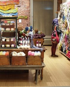 Yarns spun from natural fibers beckon from a display table; the back wall features the work of a local fiber artist. Yarn Display, Craft Booth Displays, Store Displays, Display Ideas, Wool Shop, Yarn Shop, Yarn Storage, Yarn Stash, Lion Brand Yarn