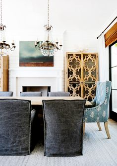 Dining space with white walls, brass and crystal chandeliers, grey and blue chairs, wood dining table, light gray patterned rug, wood floors, artwork, and large wood armoire