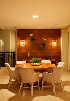 Varanda com mesa de jantar redonda der Madeira com painel de Madeira e arandelas simétricas. Decoração elegante, classico contemporânea, aconchegante.