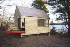 """The """"Writer's Block"""" cabin designed by Cheng   Snyder features storage for a canoe under its bed and workbench space. Located in Westport, Maine on the banks of the Sheepscott River, the 190-square-foot hideaway features windows arranged to maximize views and allow for passive heating and cooling.  Look inside the Writer's Block cabin.   - CountryLiving.com"""
