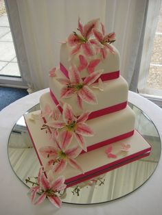 Thee tiered square wedding cake with pink sugar star gazer lilies and sugar butterflies