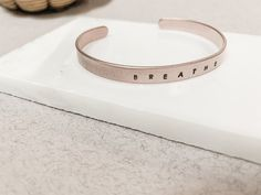 This bracelet features the phrase 'breathe' in hand stamped font. A simple  everyday reminder to stop and pause when everything is hectic.  Each of my copper bracelets are made to order and are a slim and dainty 6mm  in height and 150mm long, wrapped into an oval cuff style. This type of  finished bracelet leaves a gap open allowing you to slide your cuff onto  the wrist. Small adjustments to cuff bangles can be made as the metal has a  very slight flex to it, allowing it to be tailored to fit e
