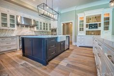 Cooking up a storm: The kitchen has new appliances and a large island in dark grey with wood floors and white cabinets