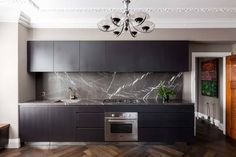 Black kitchen cabinets, black dining chairs, black backsplash, black/blue bedroom walls and cup. Black Kitchen Cabinets, Black Kitchens, Luxury Kitchens, Home Kitchens, Dark Cabinets, Contemporary Kitchen Interior, Interior Design Kitchen, Beadboard Backsplash, Kitchen Backsplash