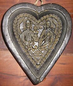 Springerle mold: wax, two people in a heart-shaped mold--maybe for a wedding?