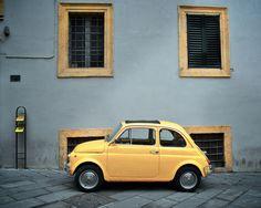 Carro com pequenos edifícios de bairros históricos por trás