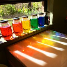 These rainbow jars reflect the creative use of light in Reggio Emilia practice. This display could be made in activities with children, involving them in the creation process and teaching them about the qualities of light. Reggio Emilia Classroom, Reggio Inspired Classrooms, Reggio Emilia Preschool, Toddler Classroom, Preschool Classroom, Classroom Ideas, Kindergarten Science, Science Activities, Space Activities