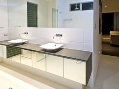mirrored front vanity plus large white gloss tiles.  Spout and taps from wall rather than vanity top.