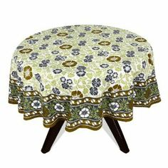 Enjoy your breakfast and tea time stories with this vibrant floral table cover. This is a round table cover with classy floral designs over it. It is made of 100% cotton and has been screen printed. The floral and leaf patterns are in olive green, pistachio green and dark grey over white background. The contrasting combinations of colors over white look very pleasing to the eyes.