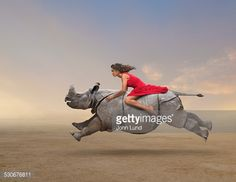 Stock Photo : Woman riding rhinoceros in rural field