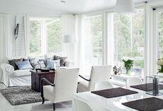 Valkoisessa oleskelutilassa on suuret ikkunat, joista on upeat näkymät luontoon. | Kesäksi järven rannalle | Koti ja keittiö | Milla Kuusinen | Kuva Kirsi-Marja Savola