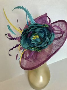 Lavender purple Sinamay Kentucky Derby Hat with embellishments of teal, purple & yellow feathers with a single teal flower. Make your statement with this stunning, hand designed, high quality piece!  *100% Brand new, hand made and high quality. *Head circumference: 22.5 and adjustable *Beautiful detail **Elegant fashion flouncing, vogue hats are perfect for horse racing events, church, the Kentucky derby, weddings, garden tea parties and charity events. ** Available to ship next business ...