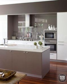 A palette of earthy, modern neutrals defines this contemporary kitchen, with units created by Kastell Kitchens.