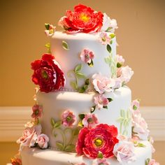 Red and pink sugar flowers topped the round wedding cake with raspberry buttercream frosting  Kakes by Karen   FL