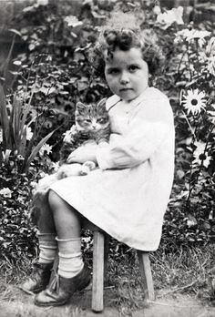 Girl with curly hair, sitting on a stool, with her cat.