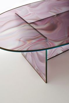 LIQUEFY | design Patricia Urquiola | GLAS ITALIA 2017 collection | High and low oval-shaped tables in tempered extralight glass, with faded and irregular decoration which takes on the colour and veins of marble. The surprising image changing effect makes the veining look dynamic and variable depending on the viewpoint. In two colours: with green hues and with pink-beige hues. The decoration is enclosed by a coordinated colour frame painted on the glass perimeter. | #glasitalia…