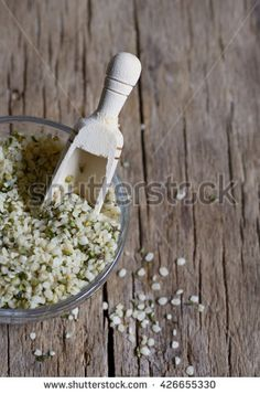 Shelled hemp seeds on wood background