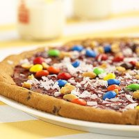 Chocolate-Chip Cookie Pizza (via Parents.com)  Ingredients        1 tube (18 ounces) refrigerated chocolate-chip cookie dough      1/2 cup raspberry preserves      1/4 cup multicolored candy-coated chocolate pieces      2 tablespoons peanuts, chopped      2 tablespoons shredded flake coconut