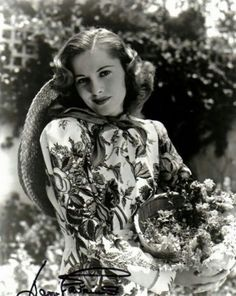 British actress Joan Fontaine gathering flowers in a matching floral dress