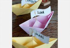 Para marcar o lugar de cada um na mesa de festa, barcos de papel com bandeirinhas no palito