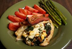 Chicken Stuffed with Spinach Feta and Bacon.  Sides of asparagus and tomato wedges.