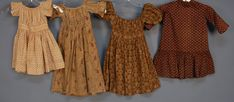 THREE LITTLE GIRLS' CALICO DRESSES, 19th C. Short sleeve with set in waist: One red on white. One blue, green and brown on dotted tan ground. One red, plum and blue floral on figured cream ground (fade marks, missing ties), Together with a brown calico dress with 3/4 sleeve, back buttons and skirt ruffle, (two buttons replaced).