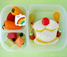Birthday Party Bento Box Lunch: For this lunch, there is a cupcake sandwich, with fruit leather details, tomato balloons and party guests. On the left are some mini sweet peppers, container of dressing for dipping and a fruit salad. Packed in an EasyLunchBox.