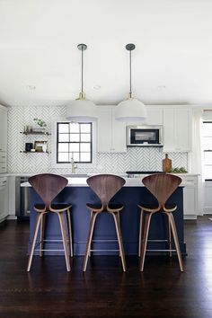 The most stunning kitchen. Love the wall and the stools.