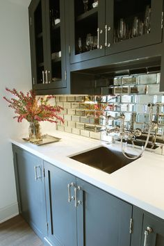 Stunning wet bar features glass-front upper cabinets and gray lower cabinets paired with mirrored subway tile backsplash and white quartz countertop framing bar sink paired with wall-mounted faucet.