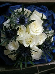 Deep Blue thistle with it's spiky forms is contrasted against these large Avalanche ivory roses, a cool combination.